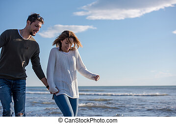 Loving young couple on a beach at autumn sunny day
