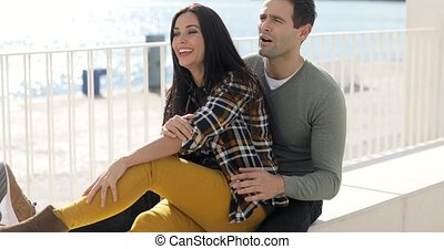 Loving young couple relaxing at the waterfront sitting in a...