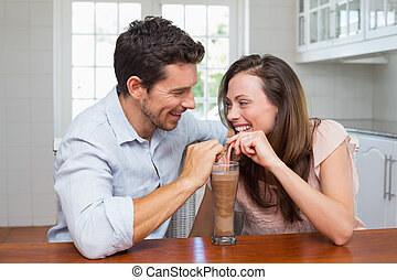 Loving young couple sharing a drink