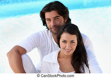 Loving young couple sitting by a pool