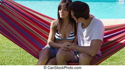Loving young couple sitting on a hammock