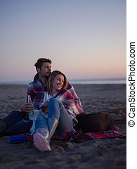 Loving Young Couple Sitting On The Beach beside Campfire drinking beer