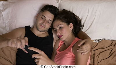 Loving young couple spending time together in bed watching a...