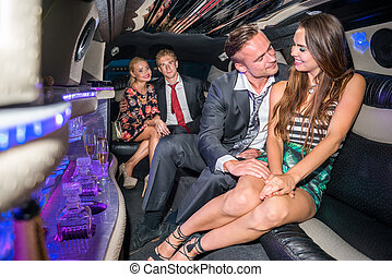 Loving young couple traveling with friends in limousine