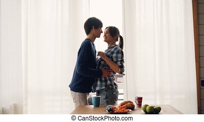 Loving young people husband and wife are dancing in kitchen...