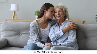 Loving young woman granddaughter embracing senior granny bonding express care