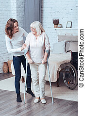 Loving young woman helping disabled old lady at home