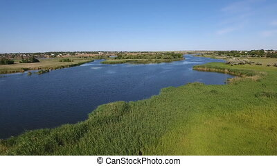 Low aerial shot of the Dnipro river with its greenary, wetland, and blue waters