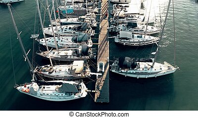 Low altitude aerial down view of a marina pier and many docked sailing yachts