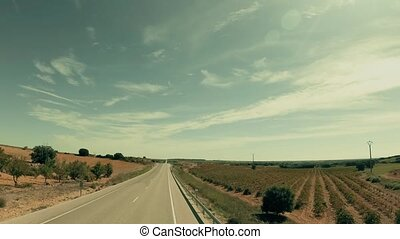 Low altitude aerial shot of a rural road in agricultural scenery in Spain