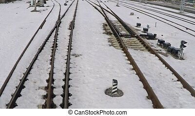 Low altitude motion aerial shot of several railway tracks and switches in snow