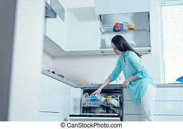Low angle, a young woman pulls clean dishes from the washing machine