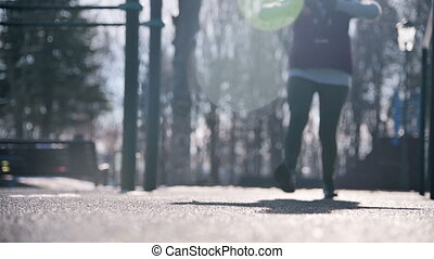 Low angle against the sun. Sports girl in the winter on the...