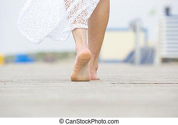 Close up low angle barefoot woman walking away