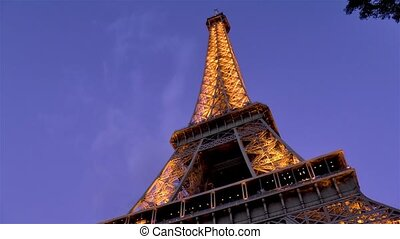 Low angle, close-up view of the Eiffel Tower at dusk, Paris, France.