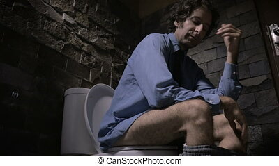 Low angle dolly shot of a man loosening his tie while sitting on the toilet