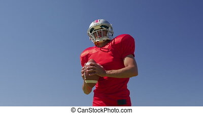 Low angle front view of a mixed-raced American football player holding a ball at a sports field in front of a blue sky, in slow motion. Track and Field Sports Training in Stadium.