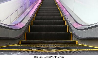 Low angle looped perspective view of modern escalator stairs. Automated elevator mechanism. Yellow line on stairway illuminated with purple light. Futuristic empty machinery staircase moving straight