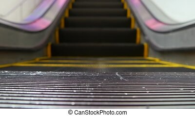 Low angle looped perspective view of modern escalator stairs. Automated elevator mechanism. Yellow line on stairway illuminated with purple light. Futuristic empty machinery staircase moving straight.