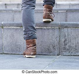 Close up low angle man walking up steps