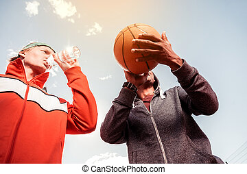 Low angle of a basketball ball in male hands