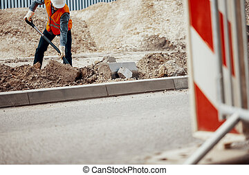 Low angle of a construction worker digging a hole in the road