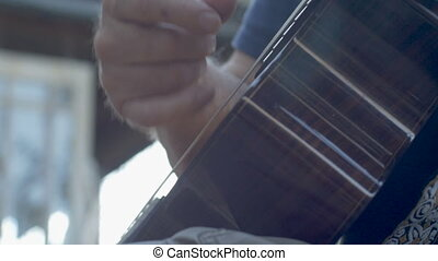 Low angle of a mans hand strumming and playing acoustic guitar