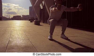 Low angle of a senior man doing squats with dumbbells