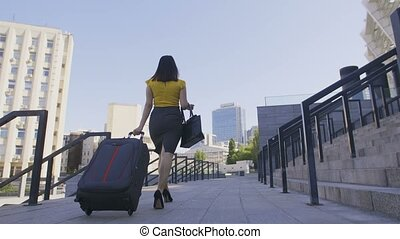 Low angle of business woman with luggage walking