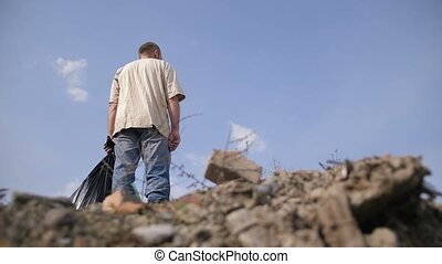 Low angle of male standing on top of garbage heap - Low...