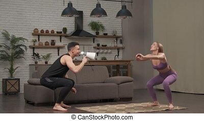 Low angle of personal coach shouting to young woman while she doing squats the rope during intensive cross training workout. a man shouting into a shout