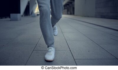 Low angle of sporty man running in the city