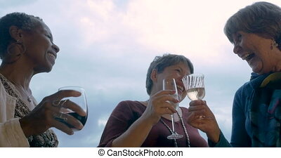 Low angle of three mature women toasting with drinks outside...