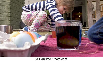 Low angle of two cute children dyeing easter eggs together in colored dye