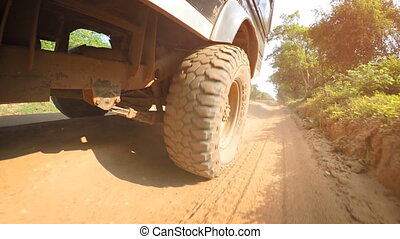 Low Angle Perspective of Wheel Rolling over Dirt Road, with Sound