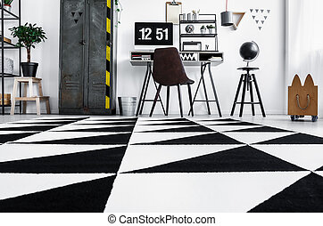 Low angle photo of home office with black and white carpet,...