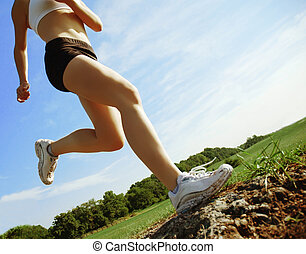 Low Angle Runner - Beautiful woman runner in front of blue...