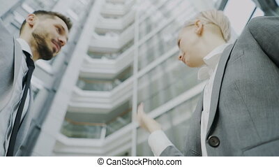 Low angle shot of bearded businessman shaking hands and talking with female business colleague in suit in hall of modern office building