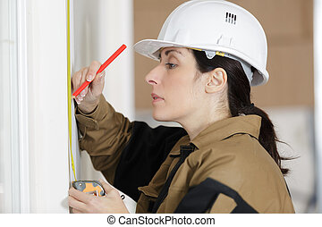 low angle shot of female carpenter working with spirit level