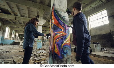 Low angle shot of graffiti painters decorating abandoned...