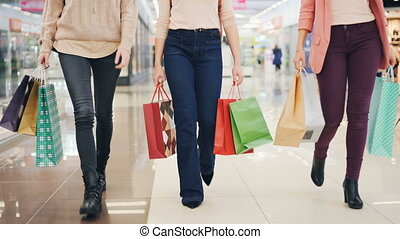 Low angle shot of group of young women walking in shopping...