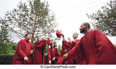 Low angle shot of joyful men and women graduating students throwing mortar-boards in the air and laughing. Beautiful summer nature and sky is visible.