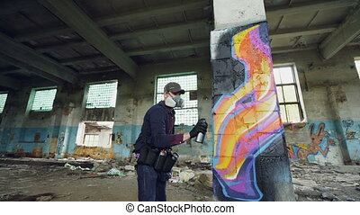 Low angle shot of young man is face mask painting graffiti on column inside empty industrial building using spray paint. Dirty damaged walls, windows and ceiling are visible.