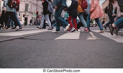Low angle slow motion shot of people's legs and feet crossing a busy city street, red bicycle passing close by camera.