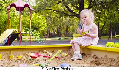 A little girl sitting in a sandbox is picking up sand - Low...