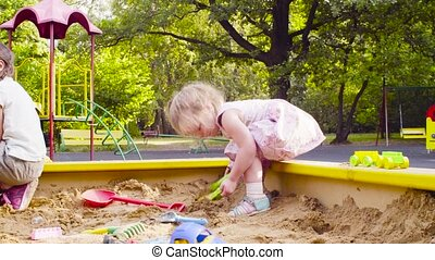 A little girl sitting in a sandbox is picking up sand