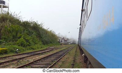 Low angle view from doors of old blue train crossing small...