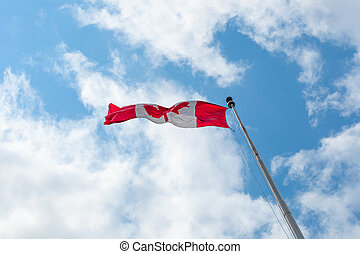 Low angle view of a Canadian flag against cloudy sky