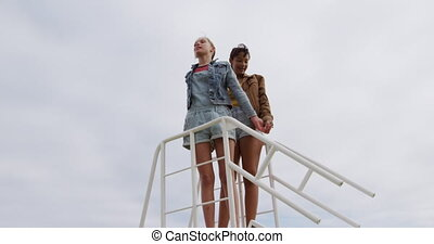 Best friends together. low angle view of a caucasian and a mixed race girl enjoying time hanging out together on a sunny day, standing together, holding hands, in slow motion.