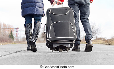 Low angle view of a couple pulling a suitcase walking side ...